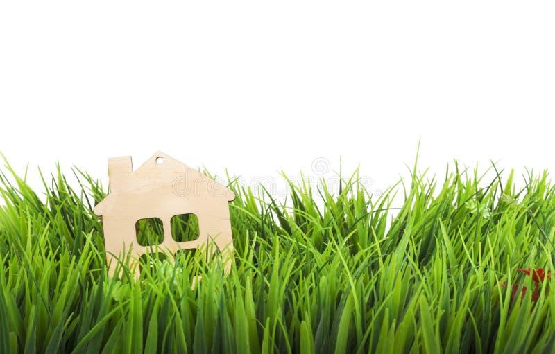 Дом игрушки деревянный в зеленой изолированной траве стоковое фото