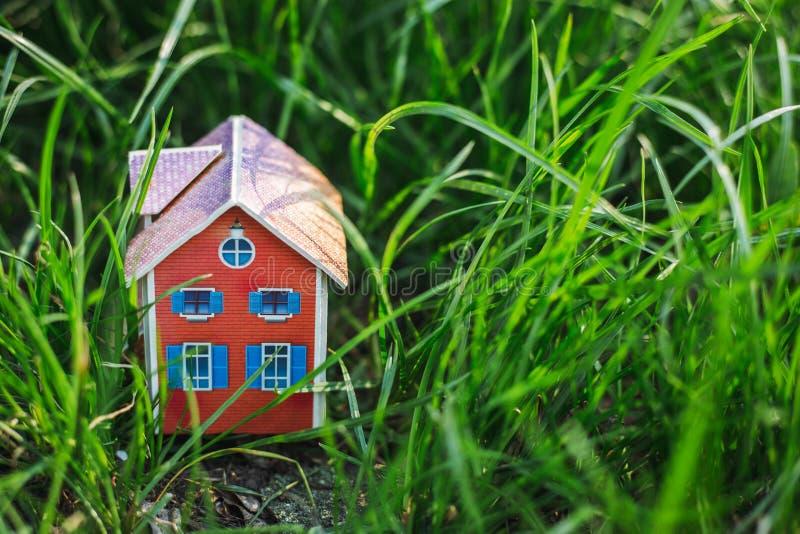 Дом игрушки на зеленой траве, месте для текста стоковые фотографии rf
