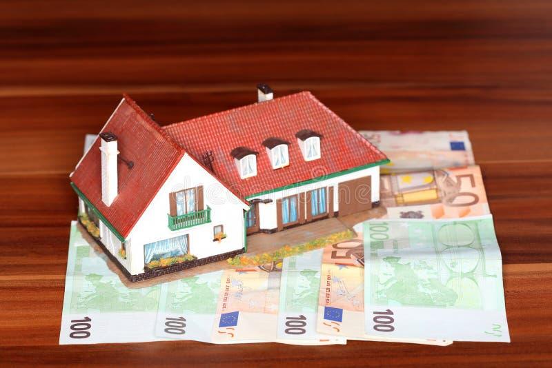Дом и деньги на деревянном столе стоковое изображение rf