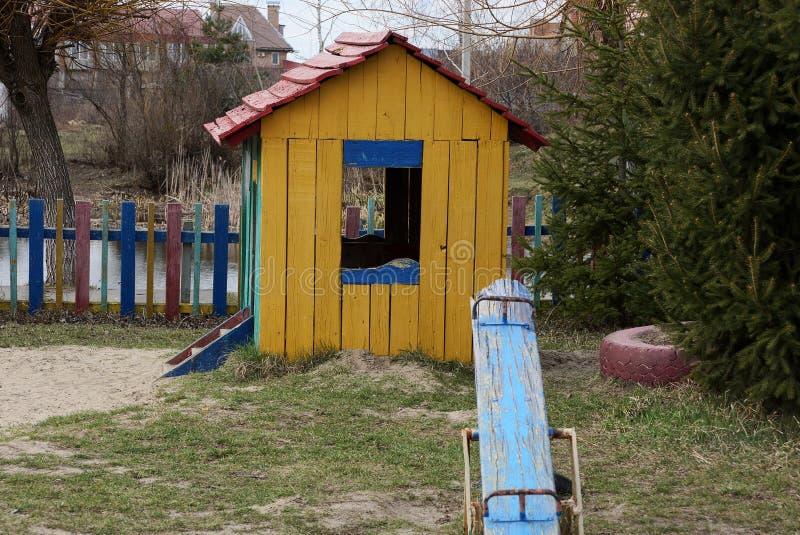 Дом и качания детей на спортивной площадке в снаружи травы стоковая фотография rf