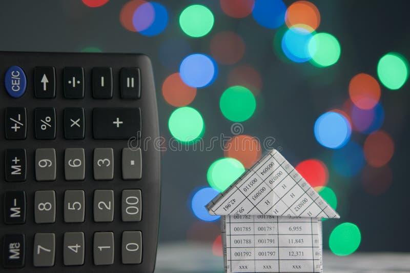 Дом и калькулятор имеют красочный круг bokeh как предпосылка стоковые изображения rf