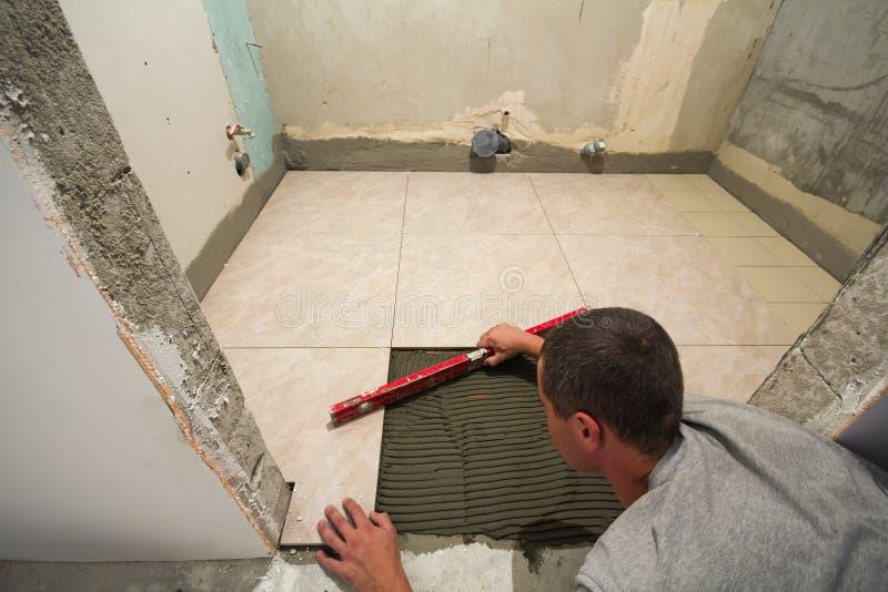 Дом кроет улучшение черепицей - разнорабочего при уровень кладя вниз с плиточного пола Концепция реновации и конструкции стоковая фотография