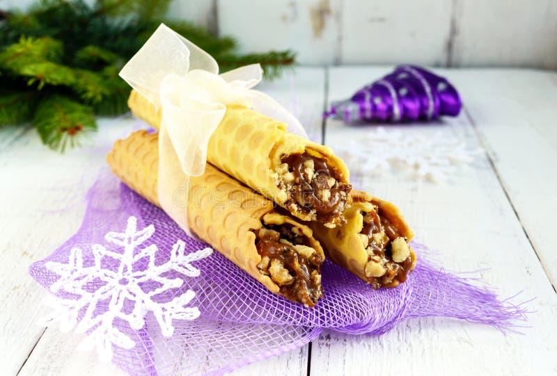 Дом меда сделал waffles в форме трубок при гайка карамельки заполняя на светлой предпосылке стоковые фотографии rf