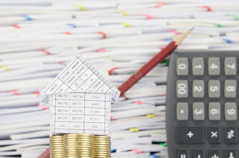 Дом на золотых монетках имеет калькулятор коричневого карандаша нерезкости постный стоковая фотография