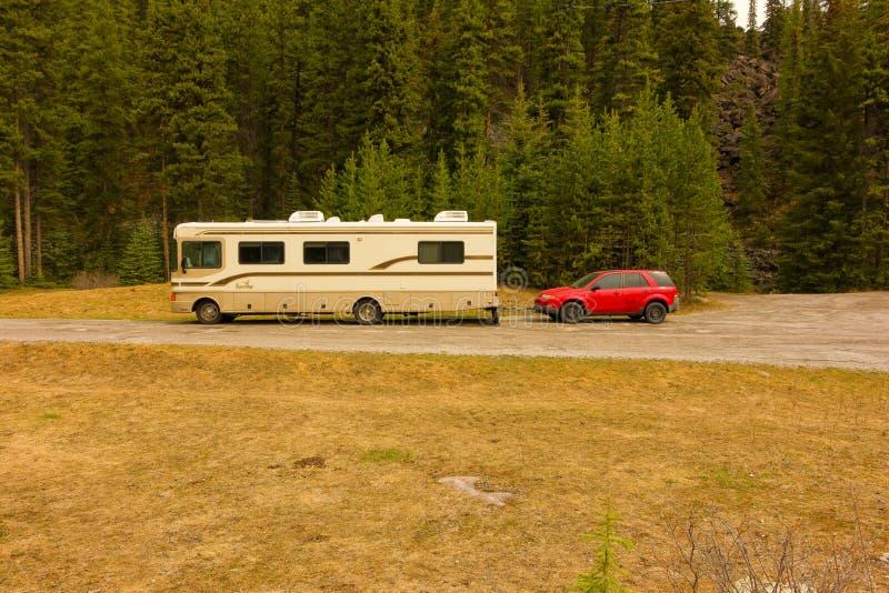 Дом на колесах буксируя автомобиль через Альберту в весеннем времени стоковое фото rf