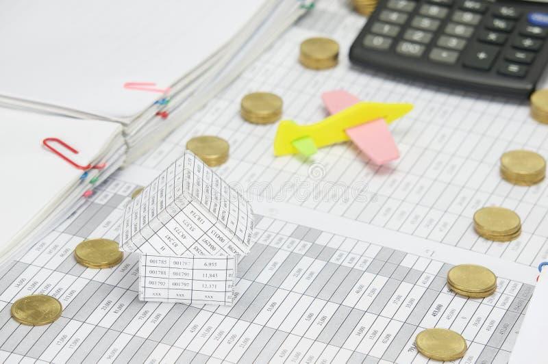Дом на финансах имеет самолет и калькулятор нерезкости как предпосылка стоковая фотография
