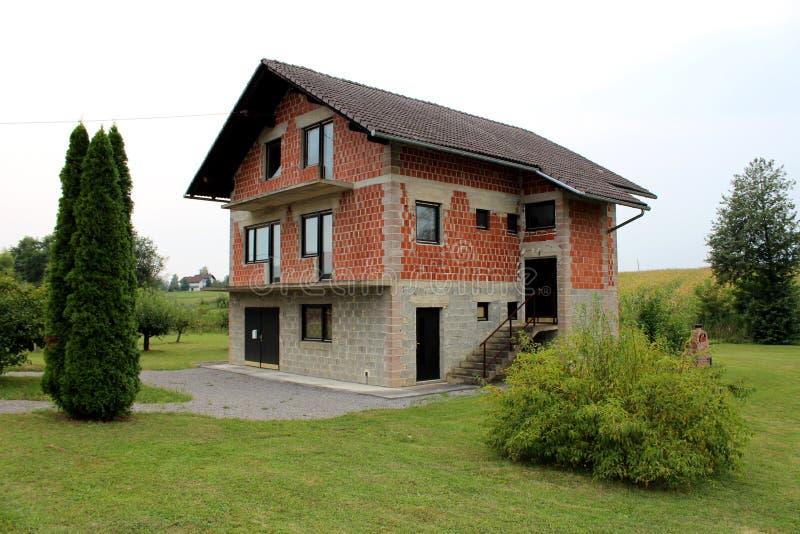 Дом незаконченного красного кирпича и серой семьи строительного блока пригородный с новыми дверями и окнами окруженными со свежо  стоковое изображение