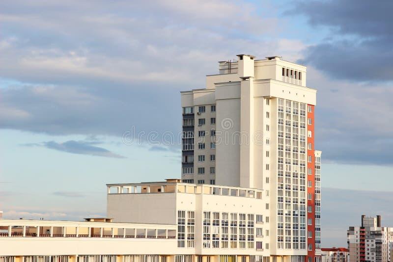 Дом нового современного блока многоэтажный на синей предпосылке неба в 4 цветах: красный цвет, апельсин, серый цвет и белизна дом стоковая фотография