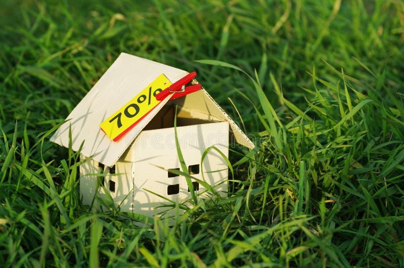 Дом от бумаги с пустой желтой карточкой с надписью 70% в зеленой траве стоковые фотографии rf