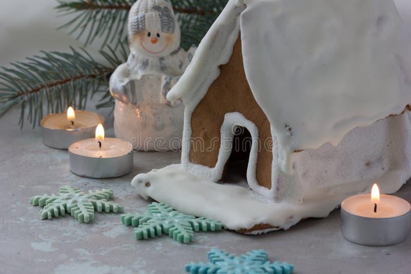 Дом пряника Snowy с снежинками рождественской елкой и глобусом на предпосылке каменной стены Домодельные печенья рождества - ging стоковое фото