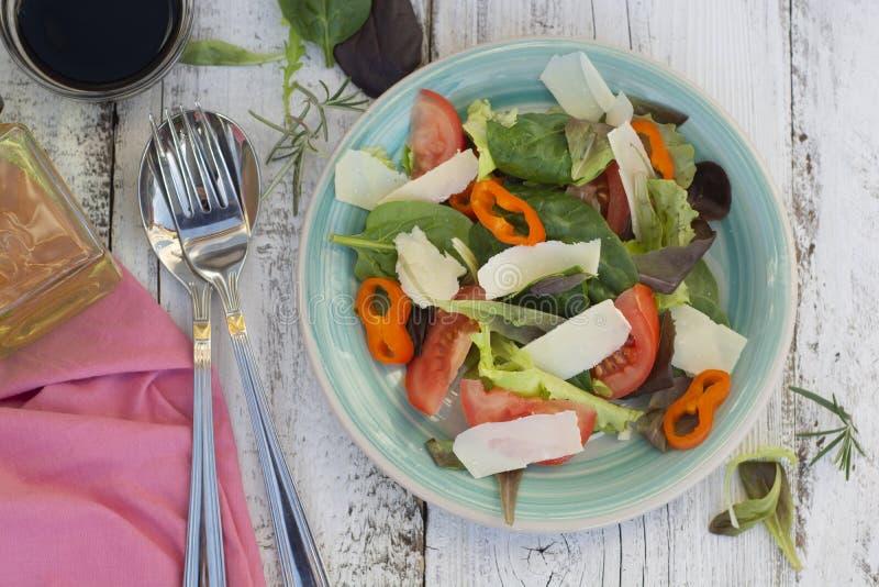 Дом сделал свежий салат с parmezan сыром, зелеными цветами и томатом Белый деревенский деревянный стол r стоковая фотография rf