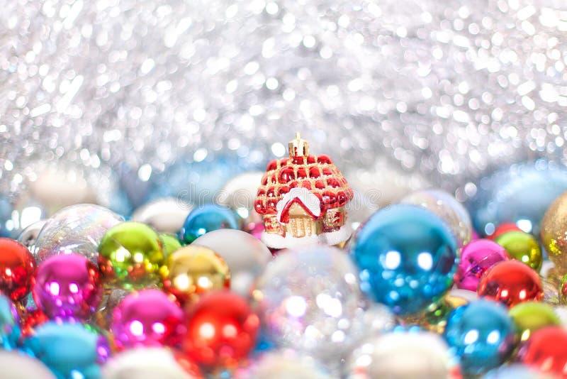 Дом сказки игрушки рождества и Нового Года красный в сугробах и снеге шариков рождества и сусаль в голубых и белых цветах стоковая фотография rf