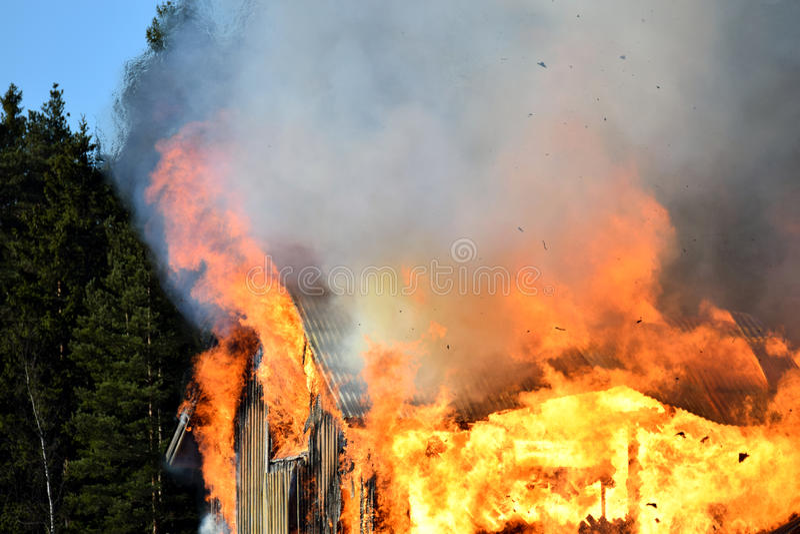 Дом совершенно поглощанный в пламенах стоковая фотография