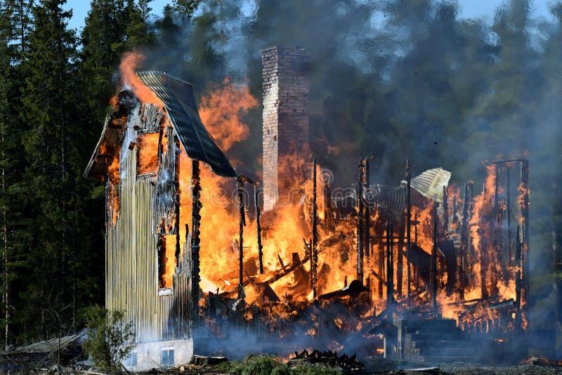 Дом совершенно поглощанный в пламенах стоковые изображения