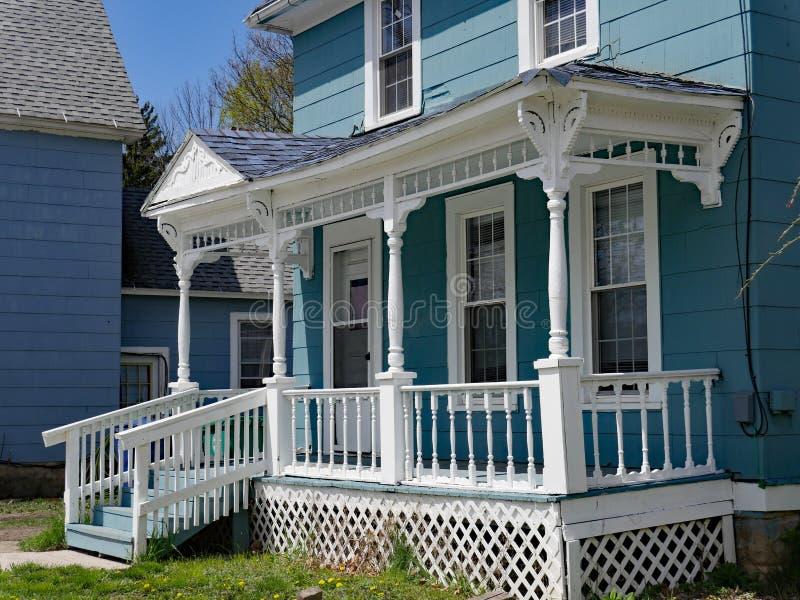 Дом со старомодными деревянными перилами шпинделя на крылечке стоковая фотография rf