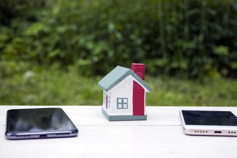 Дом стоит между 2 мобильными телефонами - белыми и черными Схематическое фото Символизирует разделение недвижимости стоковые изображения rf