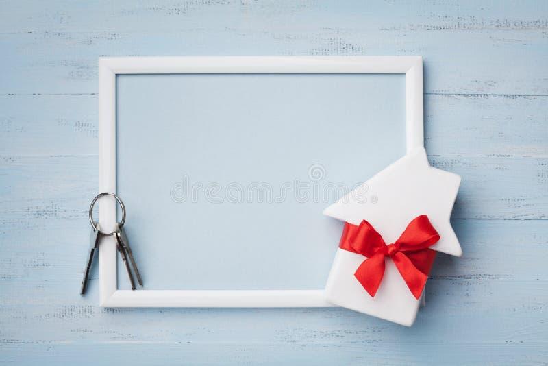 Дом с лентой, рамкой и keychain на деревянной предпосылке Покупать новый дом, планируя новоселье, подарок или продажу недвижимост стоковое изображение rf