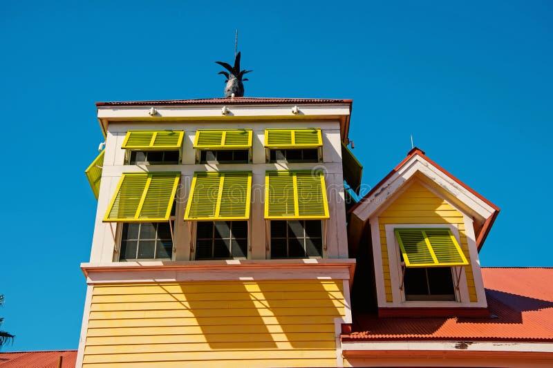 Дом с желтыми шторками окна с ананасом в Нассау, Багамскими островами стоковые фотографии rf