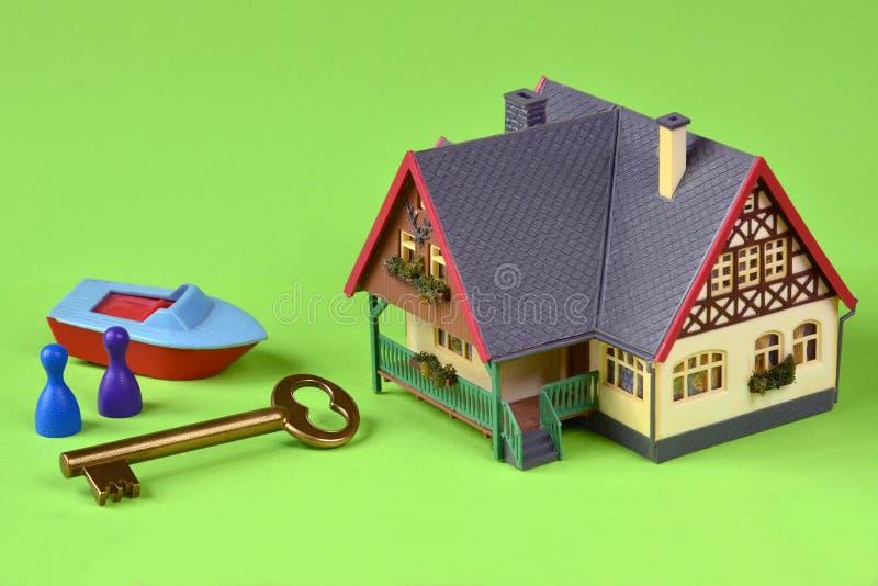Дом с ключом на зеленой предпосылке стоковые фотографии rf