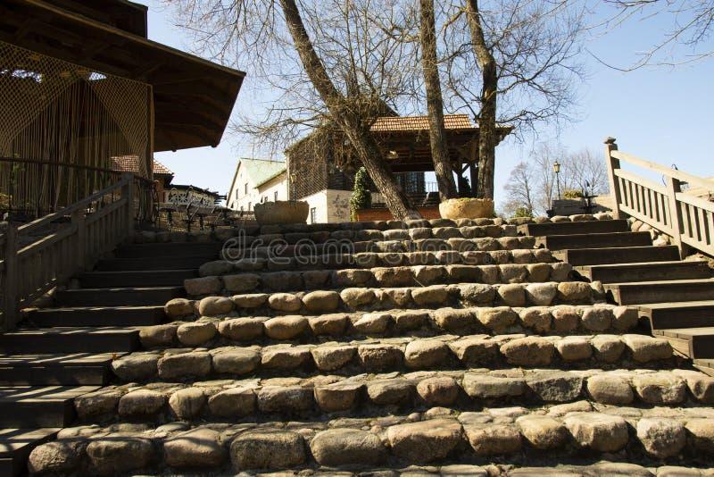 Дом с хитрыми занавесами веревочки трясет лестницы вазы и старые песчаника стоковая фотография rf
