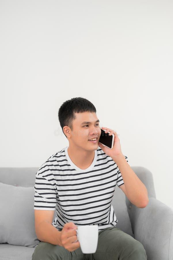 Дом, технология и концепция интернета - усмехаясь человек со смартфоном сидя на кресле дома стоковые фото