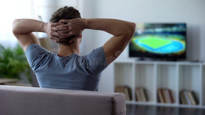 Дом футбольного матча молодого человека наблюдая, критикуя футбольную команду для поражения стоковая фотография rf