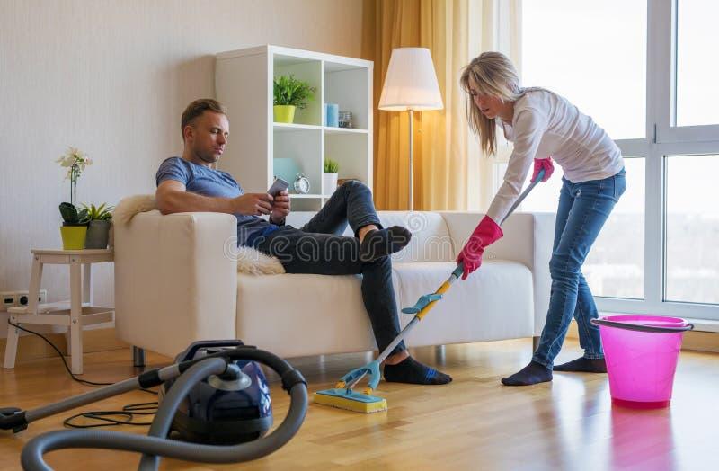 Дом чистки женщины и ` t doesn человека помогают ей стоковое изображение