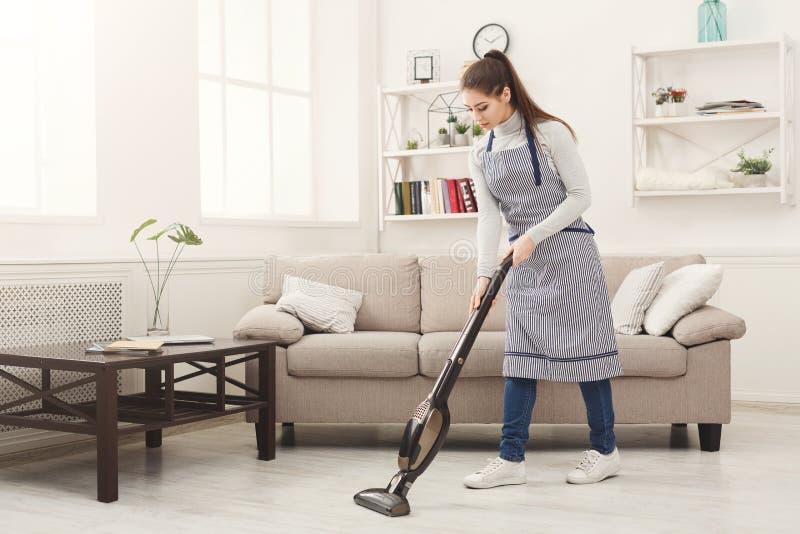 Дом чистки молодой женщины с пылесосом стоковое изображение rf