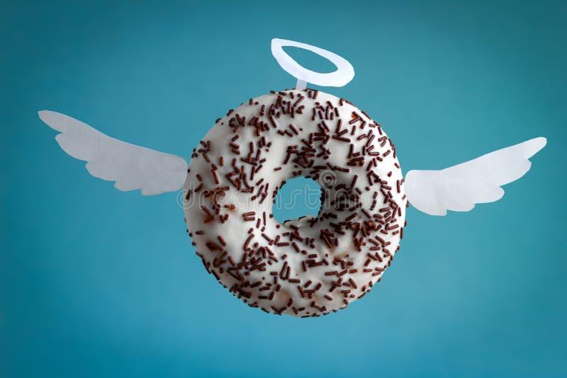 донут с белыми крыльями и nimbus на голубой предпосылке стоковая фотография rf