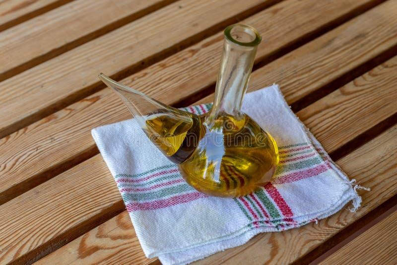 Дополнительное девственное оливковое масло в стеклянном шаре на ветоши Деревенское испанское среднеземноморское масло стоковые изображения