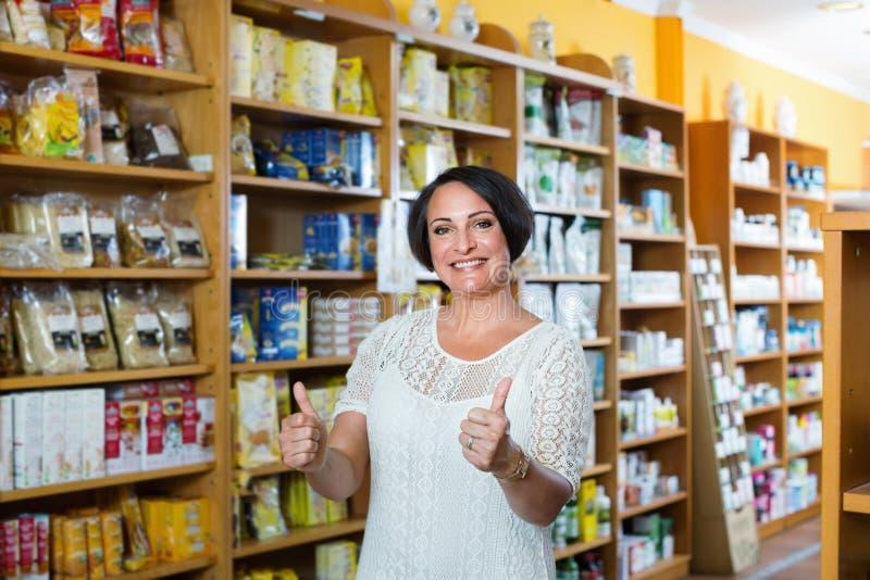 Дополнения здоровья покупок женщины в аптеке стоковые фото