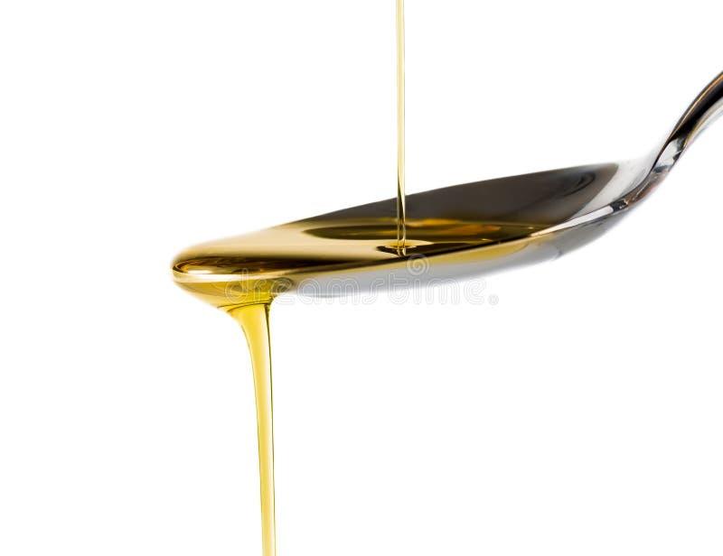 Дополнительное виргинское оливковое масло лить над ложкой изолированной на белой предпосылке стоковые изображения rf