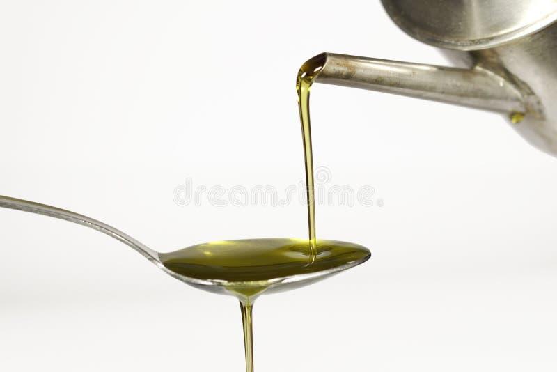 Дополнительное виргинское оливковое масло лить над ложкой на белой предпосылке стоковые изображения rf