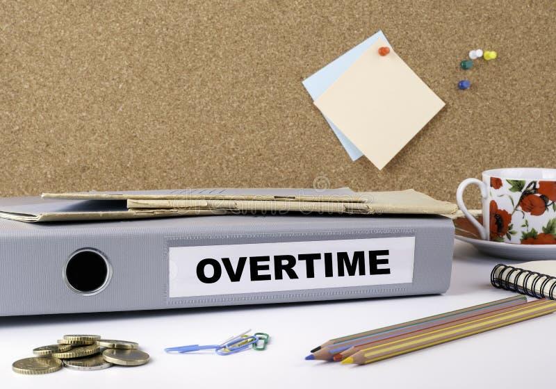 Дополнительное время - папка на белом столе офиса стоковое изображение