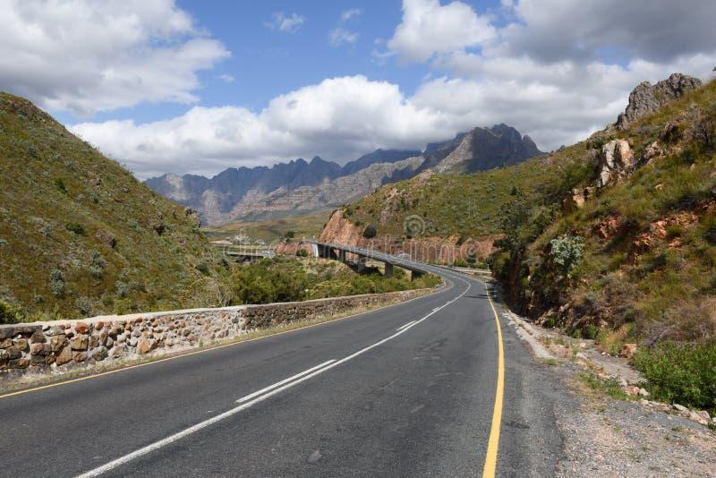 Дорога асфальта с моста скрещивания долиной однако гористой стоковое фото