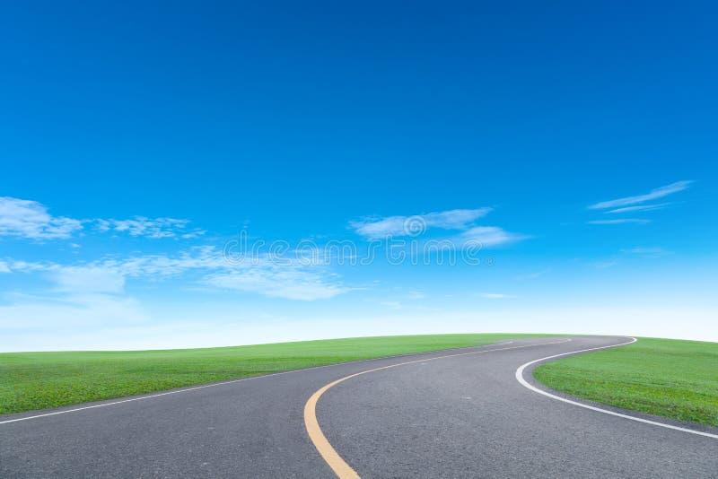 Дорога асфальта с облаком белизны голубого неба пейзажа поля зеленой травы стоковая фотография rf