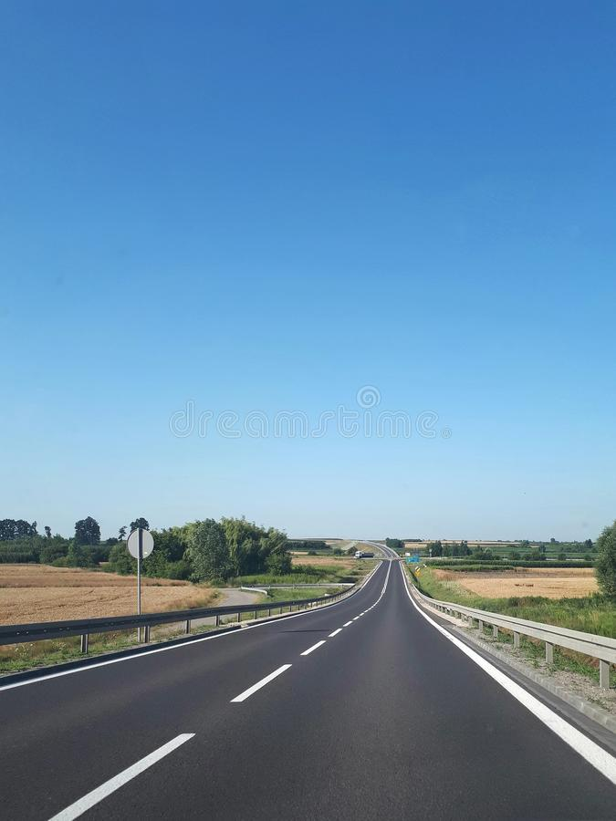 Дорога асфальта через зеленое поле на голубом небе стоковые фотографии rf