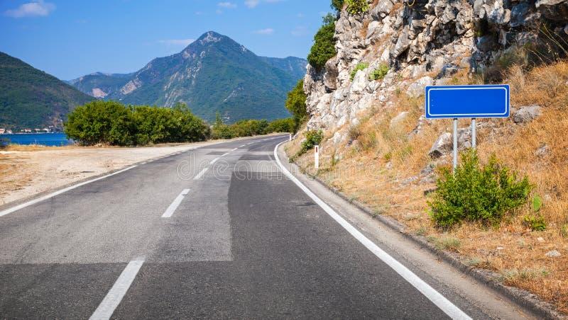 Дорога асфальта горы и пустой голубой дорожный знак стоковая фотография rf