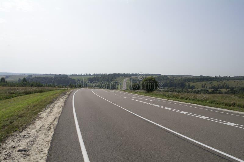 Дорога асфальта при белые маркировки идя через холмистую сельскую местность стоковое фото rf