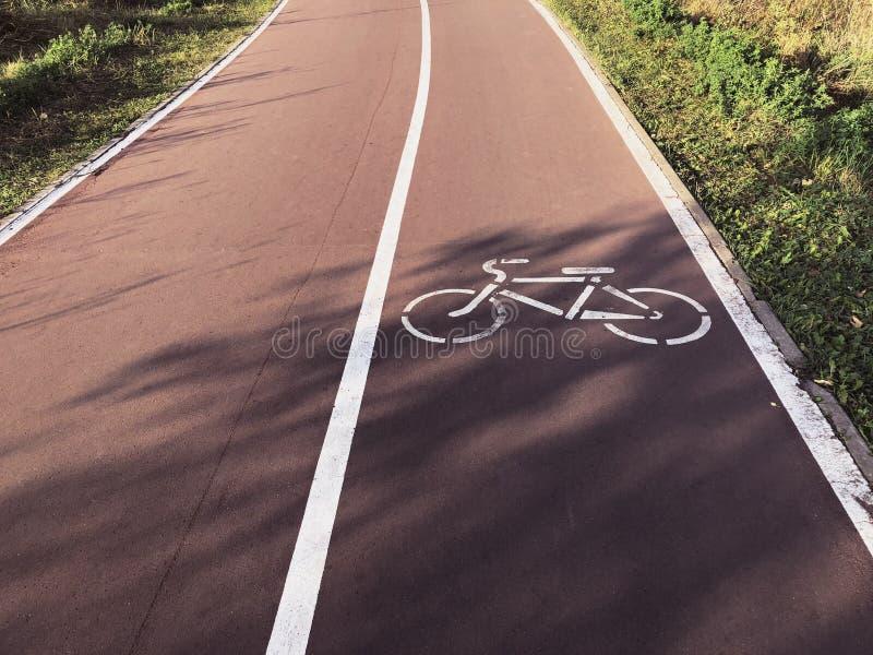 Дорога велосипеда в парке с маркировкой знака велосипеда Здоровый уклад жизни стоковое фото rf