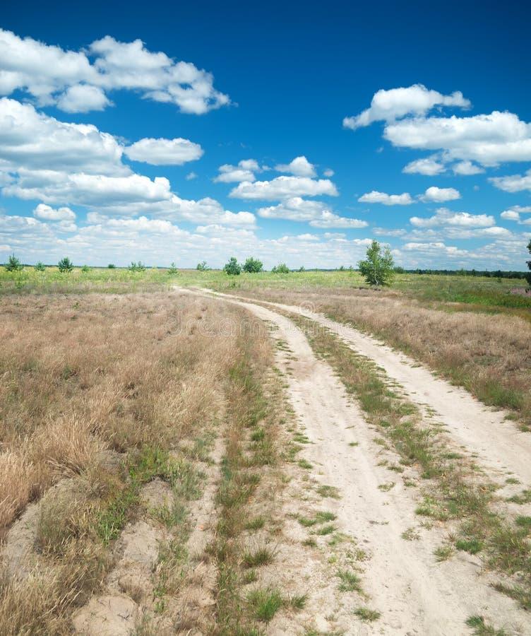 Дорога водя через поле лета стоковое фото