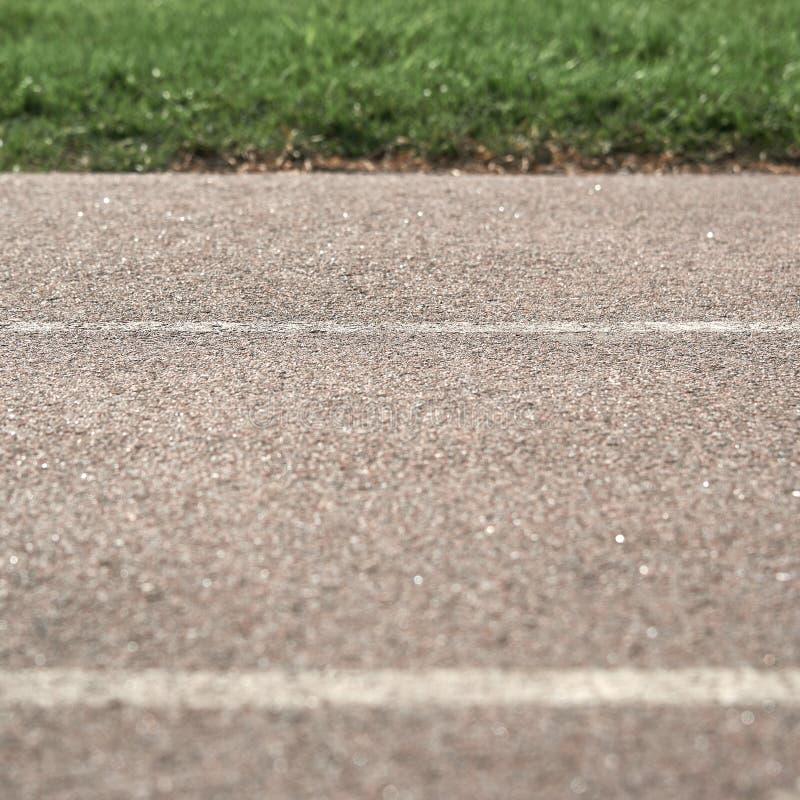 Дорога вымощенная текстурой с маркировками на предпосылке зеленой травы Часть фото в нерезкости стоковая фотография