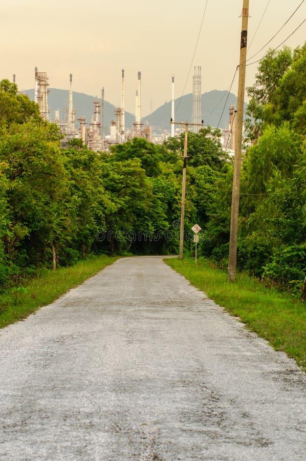 Дорога в естественном с предпосылкой индустрии нефтеперерабатывающего предприятия стоковые фото
