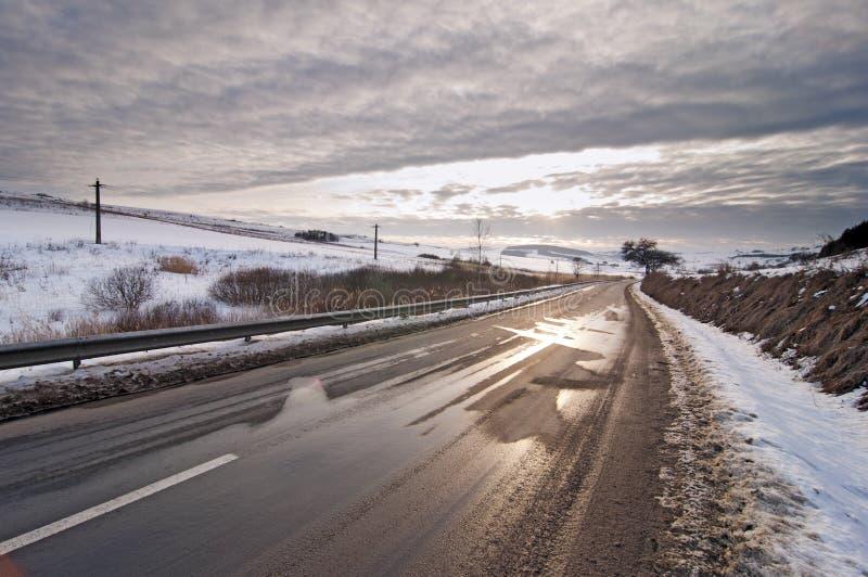 Дорога в зиме с солнцем на заходе солнца стоковые изображения