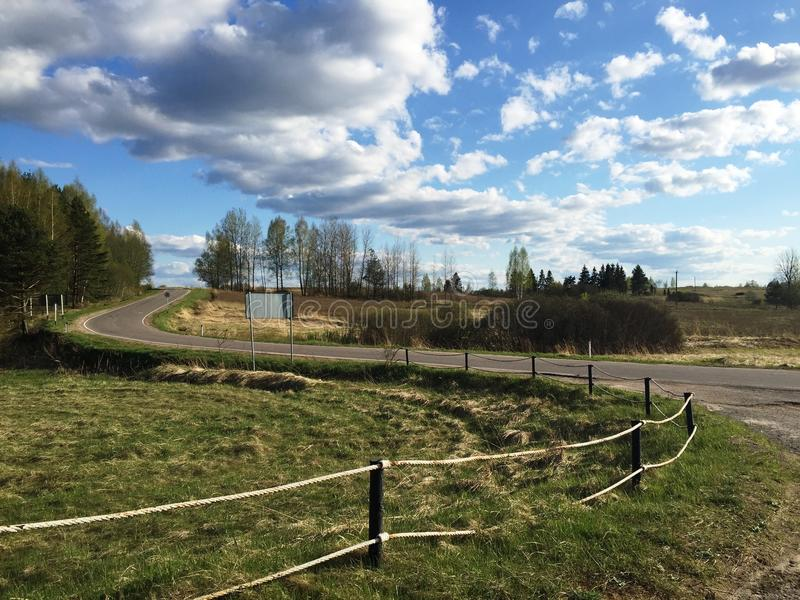 Дорога в поле, облачном небе стоковые фото