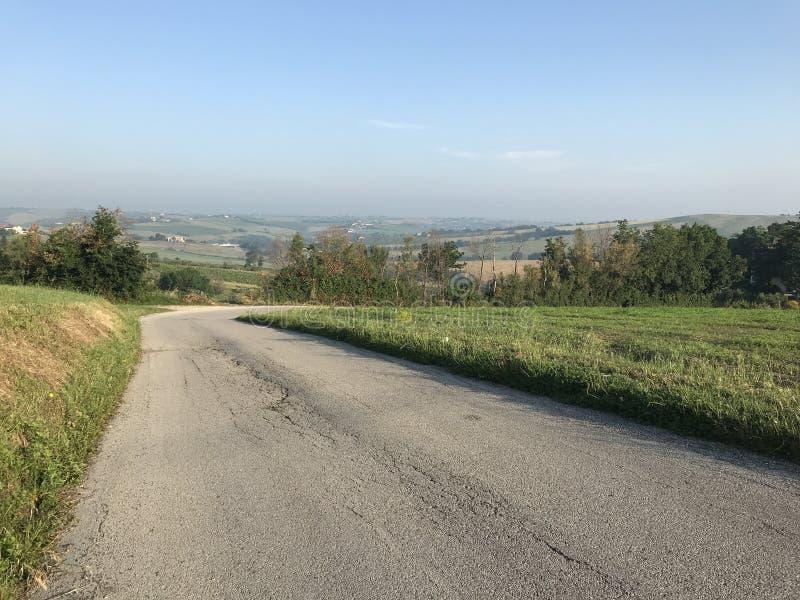 Дорога в сельской местности Pesaro и холмистого ландшафта стоковое фото