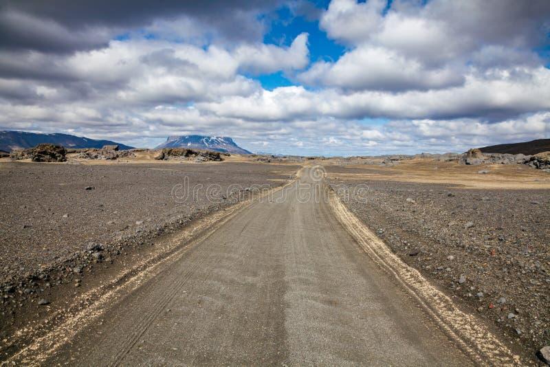 Дорога гравия к горе tuya Herdubreid через гористые местности поля лавы Odadahraun Исландии Скандинавии стоковое изображение rf