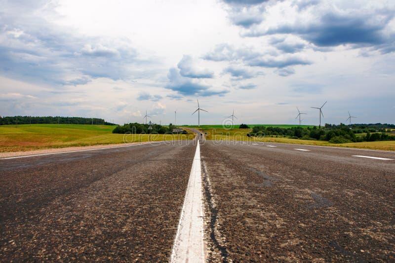 Дорога, клубы и ветротурбины стоковое изображение