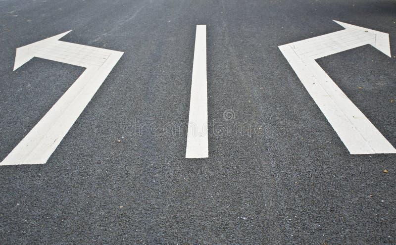 Дорога маркировк-с 2 стрелками указывая в противоположные направления стоковое фото rf