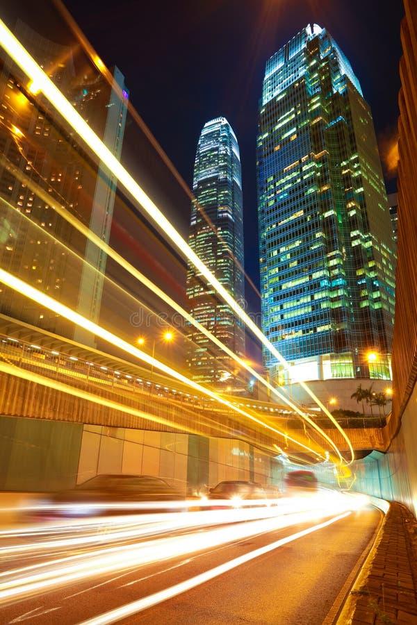 Дорога прокладывает тоннель светлые следы на современных предпосылках зданий города i стоковое фото rf